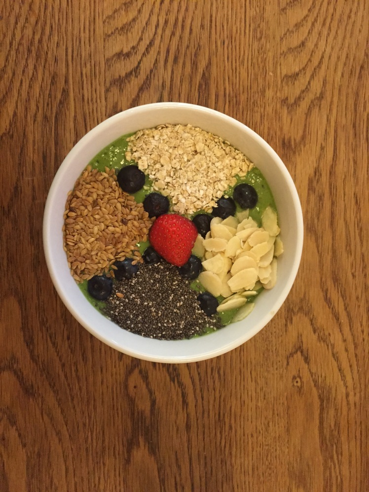 Green smoothie base topped with oatmeal, almond flakes, chia seeds, linseed, blueberries and strawberry